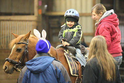 """03Mar2013__ Dimitry Hruby, age 4 of LaGrange, is helped onto a horse to ride during the Angels Haven """"Hoppin Around the Barn"""" fund raising event at Evergreen Farm in Grafton.photo by Ray Riedel"""
