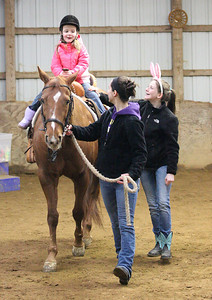 """03Mar2013__Sophie Swabb, age 4, from Elyria, enjoys a horse ride with the assistance of volunteers during the Angels Haven """"Hoppin Around the Barn"""" fund raising event at Evergreen Farm in Grafton. photo by Ray Riedel"""