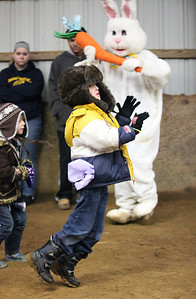 """03Mar2013__ Christopher Edmonds, age 8, passes by the Easter Bunny as he competes in a hopping race in the Angels Haven """"Hoppin Around the Barn"""" fund raising event at Evergreen Farm in Grafton. photo by Ray Riedel"""