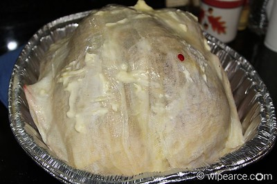 Here's the turkey, ready to head to the grill.... fully wetted down with butter, and the excess in the bottom of the pan.