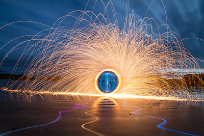 The firey sparks here are made by spinning burning wire wool, you can find out more about that here; http://photoextremist.com/steel-wool-photography-tutorial  The coloured lines on the ground were made with a coloured torch and the blue 'orb' was made by spinning a light in a vertical circle while walking around in a horizontal circle. heres a vid; http://vimeo.com/21438228