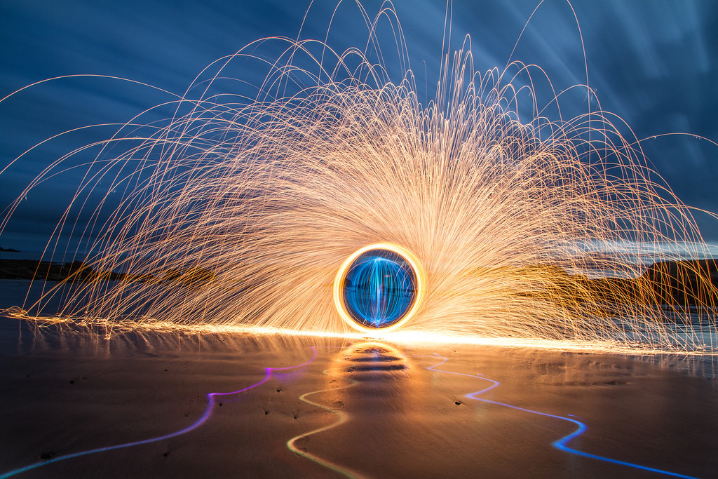 "The firey sparks here are made by spinning burning wire wool, you can find out more about that here;<br /> <a href=""http://photoextremist.com/steel-wool-photography-tutorial"">http://photoextremist.com/steel-wool-photography-tutorial</a><br /> <br /> The coloured lines on the ground were made with a coloured torch and the blue 'orb' was made by spinning a light in a vertical circle while walking around in a horizontal circle. heres a vid;<br /> <a href=""http://vimeo.com/21438228"">http://vimeo.com/21438228</a>"