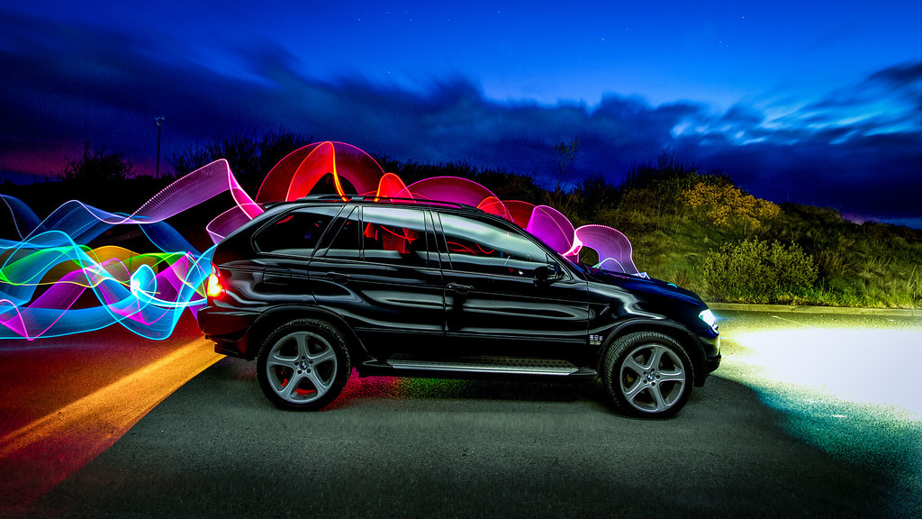This is a few layers blended. First I took a shot of the car with the lights on, then I used a Maglight with a white card reflector and walked past the car a few times to get those shiney lines, after that I went around the back of the car waving around a colour changing light wand to make the coloured ribbons. Once all the photography was done I layered all the frames in Photoshop and set the blending to 'lighten'.