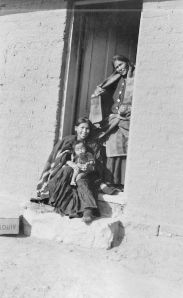 """According to Elizabeth Clark Von Gausig """"Laundress at boarding school with her daughter and grand daughter—standing in door of trading post around 1915.""""<br /> <br /> 3.25x5.5 negatives shot by Howard Clark on the Navajo Reservation near Window Rock, ca. 1913 while he was a Presbyterian minister there. These negatives belong to his daughter, Betty Von Gausig."""