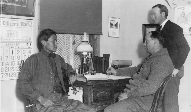 "According to Elizabeth Clark Von Gausig: ""left to right: Guy Clark (Navajo interpreter), Mr. Butler (Mennonite), Papa (Howard Clark) in Howard Clark's Fort Defiance office."" 1913<br /> <br /> 3.25x5.5 negatives shot by Howard Clark on the Navajo Reservation near Window Rock, ca. 1913-19 while he was a Presbyterian minister there. These negatives belong to his daughter, Betty Von Gausig. Howard Clark is the gentleman in the upper right."