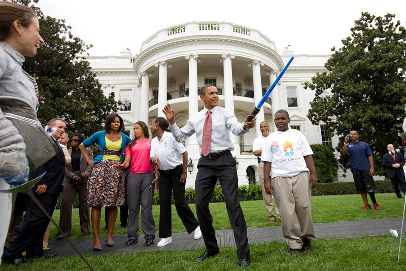 President Barack Obama uses a light saber as he watches a demonstration of fencing at an event supporting Chicago's 2016 host city Olympic bid, on the South Lawn of the White House in Washington. At rear is Chicago Mayor Richard Daley and first lady Michelle Obama.<br /> <br /> Photo by Brooks Kraft/Corbis