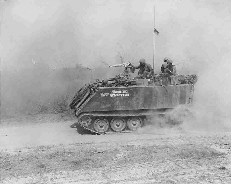 This was probably taken while we were moving on Hwy. #13, ( Thunder Road ).  Notice the towel wrapped around the M-60 machine gun mounted on top of the Flame Thrower, the towel was used to keep the dust out of the gun while on the move, it was put on in such a way as it could be snapped off and the gun immediately put into use.  Also notice how we carried our C-Rations, water cans, Ammo and other gear on top of the Track, this provided added protection during a fire fight and allowed more room inside the Track for the crew.