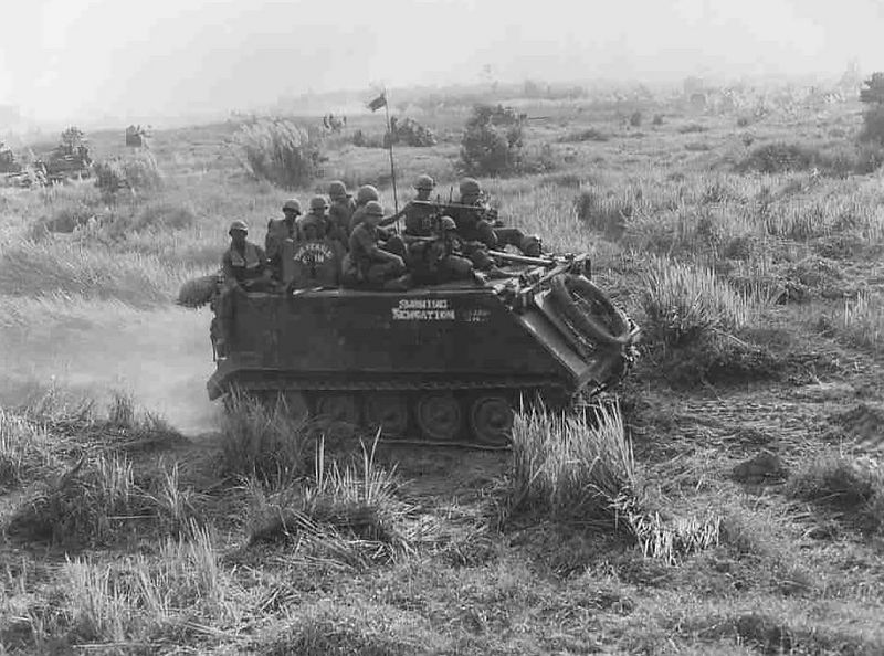 "In this photo you can see how when we were very lucky we had Infantry support.  We would transport the ""Grunts"" to the battle where they would dismount and provide protection against any enemy that would get in-between the Tracked vehicles.  There is a common mistake made about Infantry and Armor, most folks think that  Armor protects the Infantry, actually, it's just the other way around.  Armor supplies the fire power, Infantry keeps the enemy from getting in close to the Armor where the Armor can not defend itself.  When ever we had to operate in the deep jungle or the rubber plantations without the Infantry we were sitting ducks and took many more casualties, here's to the Grunts."