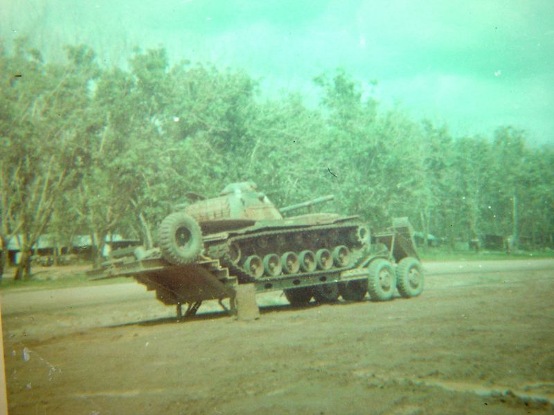 This is a damaged M-48A3, loaded on a flatbed trailer. It will be hauled to the rear and repaired or stripped for parts if it is too badly hit.