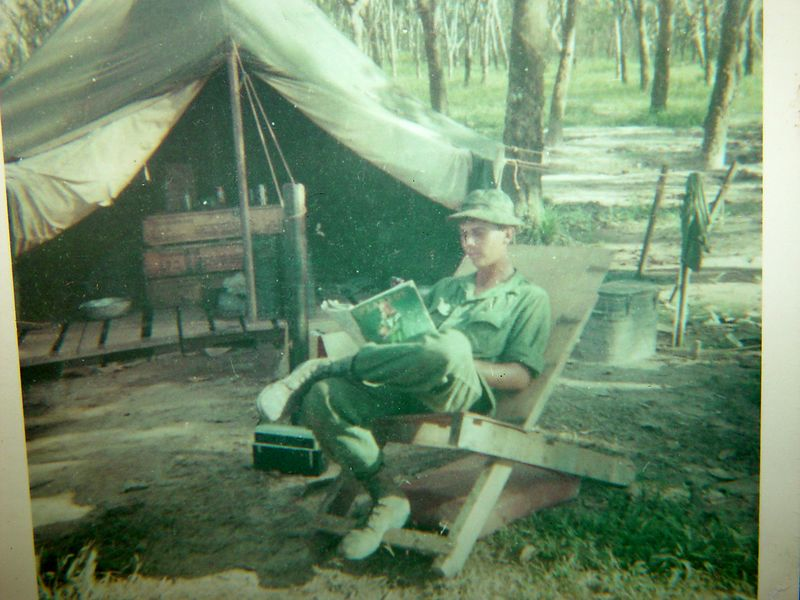 Judging from the cover of the Playboy magazine I am reading, this should be late 1967 or early 1968.  This was taken in front of my tent when we were working the area around the Base Camp at Lai Khe.  Notice how we used the empty pallets that supplies came in on, the floor of the tent and my chair are old pallets.                             .