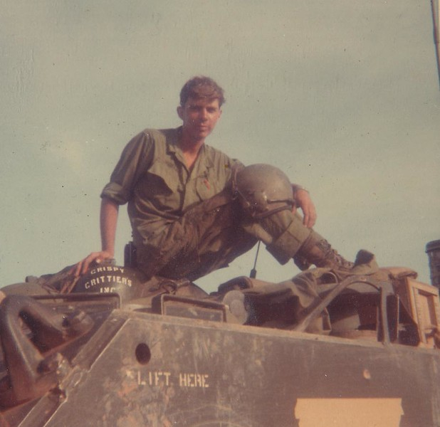 "This photo is of me sitting on top of the flame gun, under my right hand you can see where I had painted, ""Crispy Critters Inc."".  in the lower part of the photo you can see a area covered in masking tape, we would cut  letters or a design into the tape and use it as a stencil when we painted on the sides of our Tracks.  Into that tape I would cut the name ""Burning Sensation "" which is what I called my ""Zippo"".  To some folks things of this nature might seem gross, ""humor"" or what passes for it in a combat zone can sometimes have a dark side."