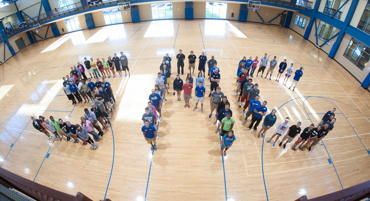 Staff of the Student Recreation Center pose and form SRC on the basketball floor