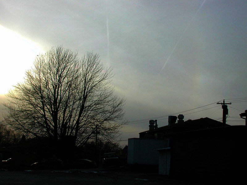 """March 6, 2007 this is the much fainter """"sun dog"""" and it is just visible in this image as the rainbow glow to the right of the diagonal contrail. It also appears to have arc appearence."""