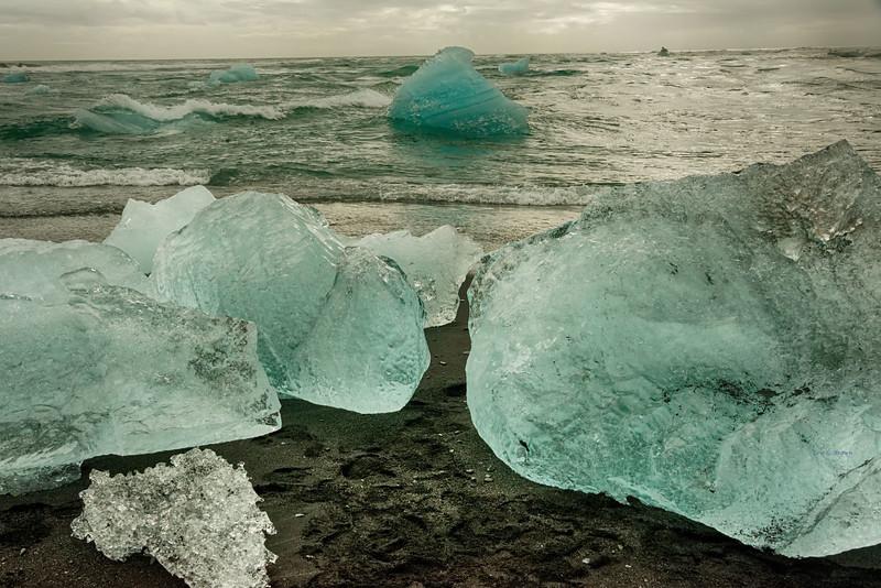 Icebergs washed ashore on black beach