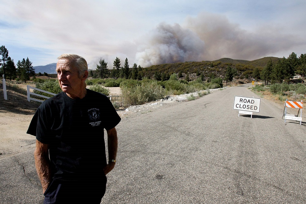 Description of . Dean Ness stands on Morris Ranch Rd. after he was ordered to evacuate from his home from the Mountain Fire near Lake Hemet on Tuesday July 16, 2013. The 14,200 acre forest fire near Idyllwild Calif., has caused Idyllwild and adjacent communities east of Highway 243 to issued mandatory evacuations for hundreds of homes Wednesday. (AP Photo/The Press-Enterprise, Frank Bellino)