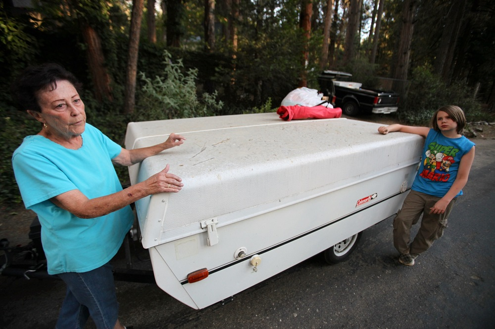 Description of . Dustin Leadbetter,11, right, prepares to evacuate his home on South circle Drive in Idyllwild,Calif., Wednesday, July 17,2913 with help from family friend Mary Postel after mandatory evacuations were made as the Mountain Fire nears. (AP Photo/The Desert Sun, Richard Lui)
