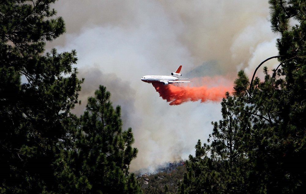 Description of . An air tanker makes a drop on the Mountain Fire near Lake Hemet, Calif. on Tuesday July 16, 2013. The 14,200 acre forest fire near Idyllwild Calif., has caused Idyllwild and adjacent communities east of Highway 243 to issued mandatory evacuations for hundreds of homes Wednesday. (AP Photo/The Press-Enterprise, Frank Bellino)