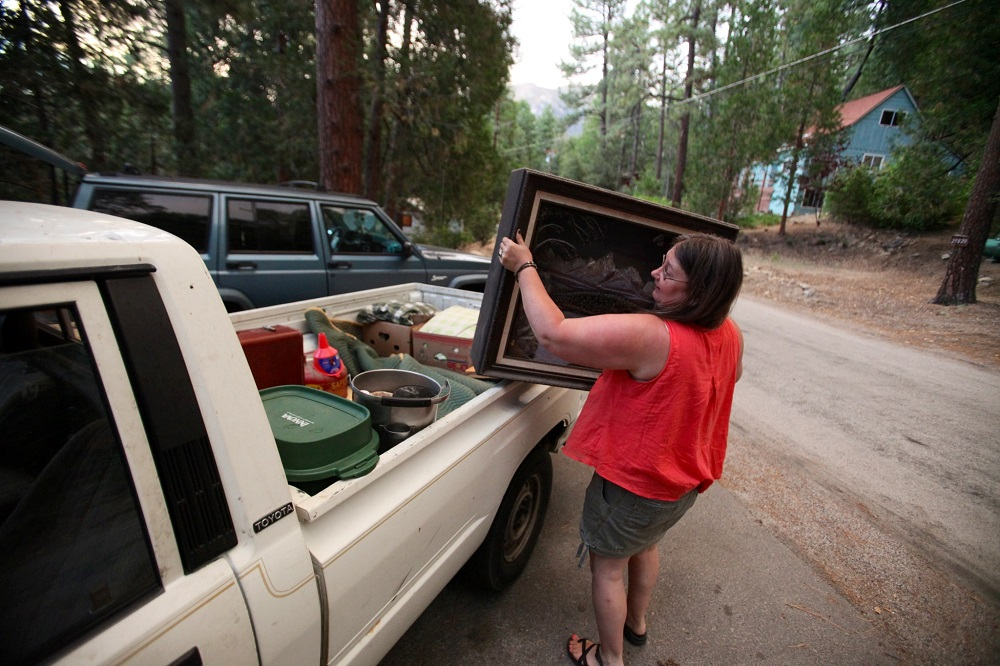 Description of . Deidra Wood evacuates her home with 3 dogs, one cat and a fish ahead of the approaching Mountain Fire in Idyllwild Calif., Wednesday, July 17, 2013. Some 6,000 residents and visitors in Idyllwild and smaller surrounding communities had to clear out Wednesday as the fire in the mountains southwest of Palm Springs surged in size and began burning toward towns, the U.S. Forest Service said. (AP Photo/The Desert Sun, Richard Lui)