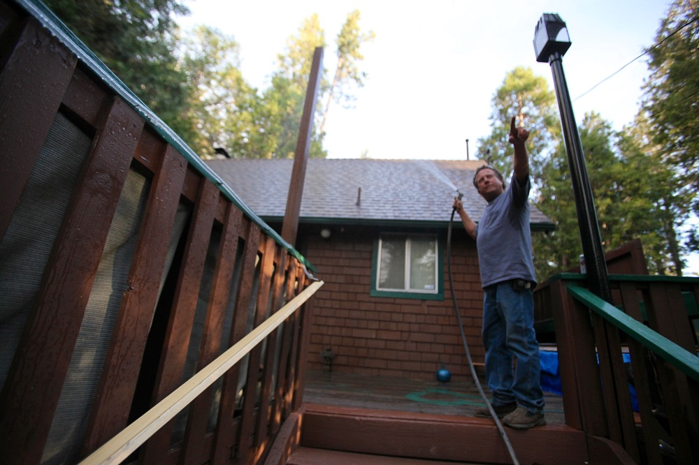 Description of . Phillip Canaday waters down his roof at his house on South Circle Dr. in Idyllwild, Calif. and points to smoke from the Mountain Fire Wednesday, July 17, 2913. (AP Photo/The Desert Sun, Richard Lui)