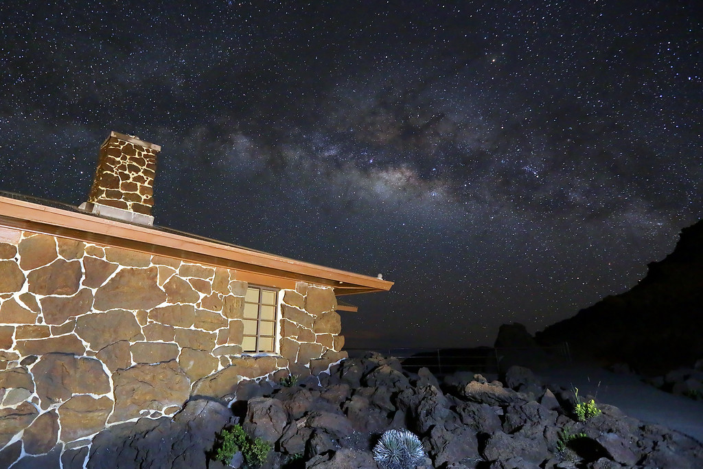 The top of Haleakala Crater on the island of Maui, Hawaii.   At 10,500 feet above sea level, with no city light pollution... the night sky is spectacular!   Here the Milky Way rises over the Visitor's Center at the rim of the crater in Haleakala National Park.
