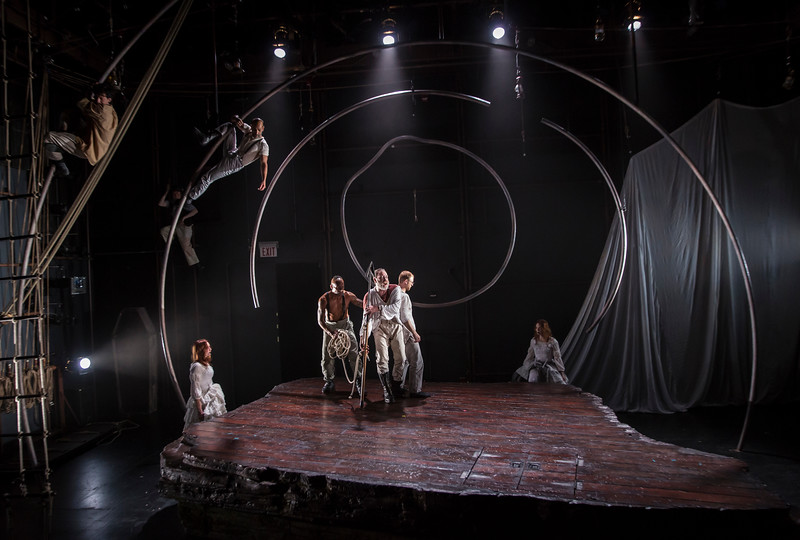"<h2>MOBY DICK (Lookingglass Theatre)</h2> <h4><p><strong>*Jeff Award Best Production - Play</strong></p><p>""<strong>What is remarkable about Courtney O'Neill's design</strong> for ""Moby Dick"" is that it avoids such familiarities, substituting instead a slice of deck emblematic of land itself, immediately plugging in to the Melvillian theme of our obsession being not so much the expanse of the raging seas but the precise spot where the rules of the land stop and the primal conflicts of the sea begin.  <br><strong>Doing the best work of her career,</strong> O'Neill has come up with a series of curved poles, structures that can be masts, sure, but that also can form the carcass of the great antagonistic beast, thus suggesting that Moby Dick is on board the Pequod even before the vessel sets sail from Nantucket. For Moby Dick lurks inside us all. Otherwise he's merely the kind of whale you cruise to Alaska to hope to see.""  --Chicago Tribune </p><p> ""Performers scramble nimbly on <strong>Courtney O'Neill's ingenious set</strong>, dominated by a series of curved ribs that resemble the yards and masts of the Pequod and the massive bones of a whale."" --The Orange County Register</p></h4>"