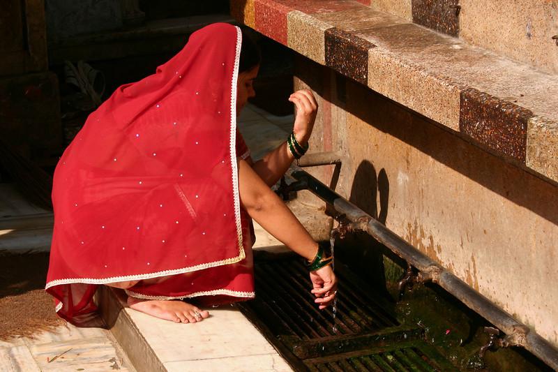 A woman washes for prayers at the shrine of Hazrat Nizamuddin in Delhi