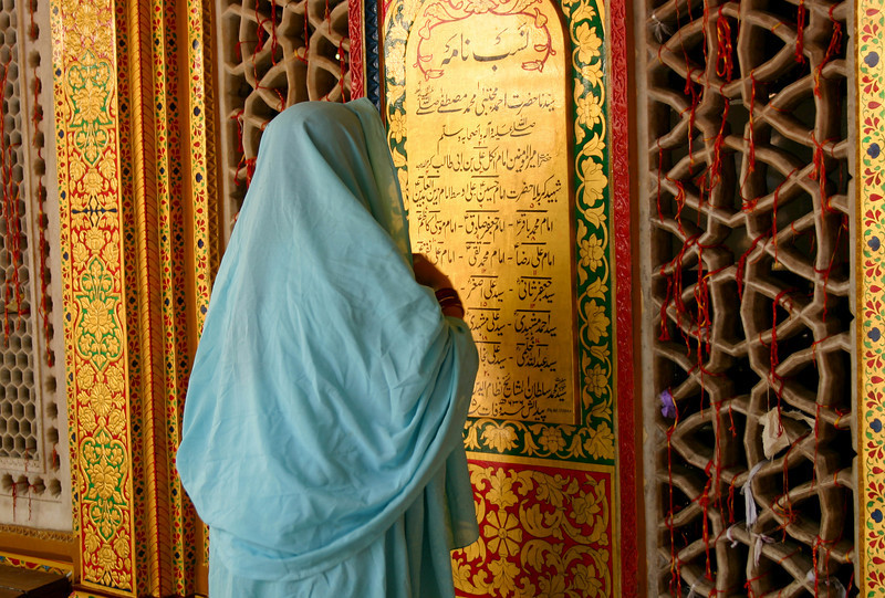 A woman prays at the shrine of Hazrat Nizamuddin in Delhi. Women are not allowed inside where the actual tomb is, but they can pray from the outside. Many tie red threads to the grating to aid their prayers being heard.