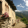 A family rests in front of their home in the Pir Panjal range of the Himalaya in Chamba District, Himachal Pradesh
