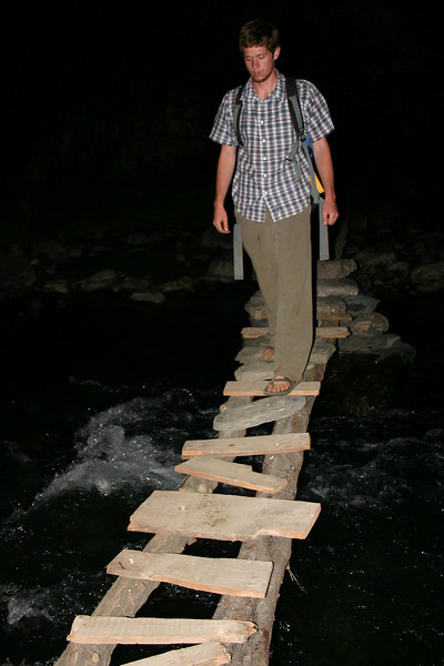 Jeff braves a precarious bridge over an icy mountain stream in the dark