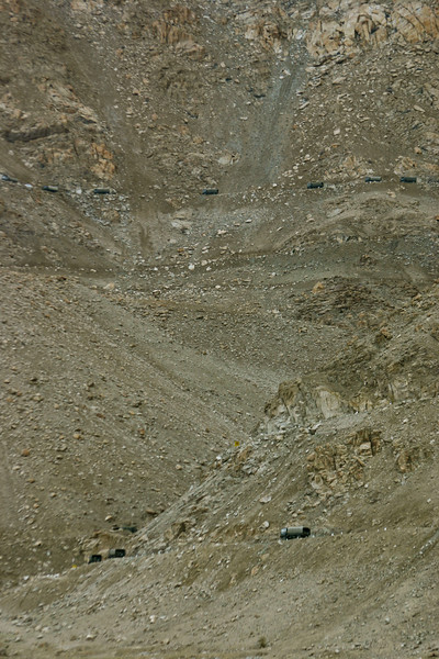 An army convoy snakes up a series of switchbacks on a steep mountainside