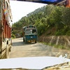 Yes, we are passing a large truck on a narrow road. Yes, there is an oncoming truck rapidly approaching. Yes, this is India.