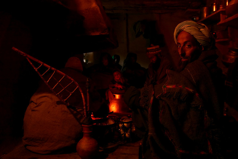 Men gather around a fire in a Gujjar home. At left is a traditional hookah with a bamboo pipe.