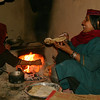 Making flat bread in a traditional hearth. Gujjar women in this area often braid their hair into very fine braids.