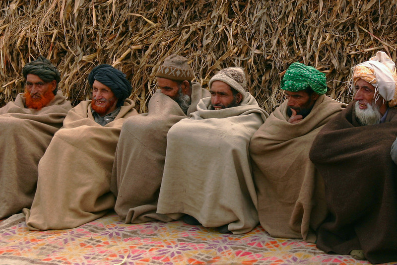 Gujjar elders wrapped up against the cold in front of a pile of corn husks at an outdoor wedding ceremony