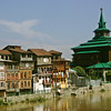 A row of homes and a large mosque line the banks of the Jhelum in Srinagar, Kashmir