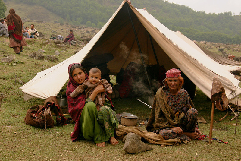 A Bakarwal family rests in front of their tent