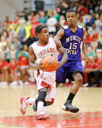 Don Knight / The Herald Bulletin<br /> Anderson's Djuan Peel drives into the paint as he is guarded by Muncie Central's Marcus Dukes on Thursday.