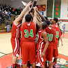 Anderson huddles around their trophy after beating Pendleton Heights 46-41 for the County Tournament Championship on Friday.