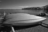 A row of shiny aluminum canoes lined up on a beach overlooking Puget Sound.