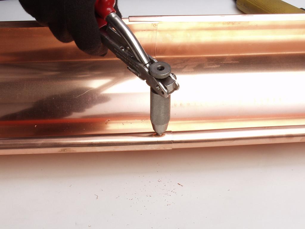 "Using a pop rivet gun place a rivet in the drilled hole.  <a href=""http://www.abraingutters.com"">http://www.abraingutters.com</a>"