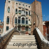 steps on a bridge over a canal in venice leading to a large italianate house with a tower