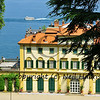 symbols of wealth. An italian mansion by the side of a lake with a large pleasure boat passing by
