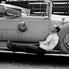 20th October 1930: American silent screen comedian and actor Buster Keaton (1895-1966) is overcome with exhaustion on the side of a convertible motor.