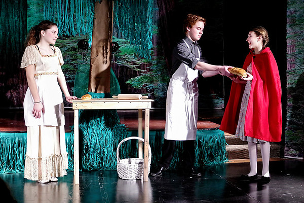 """Mark Maynard   for The Herald Bulletin<br /> The Baker's Wife (Teddi Bishop) and the Baker (Tyler McCorkle) give a loaf of bread to Red Riding Hood (Lilly Thomas) for her Granny in Alexandria Commons Theatre's production of """"Into the Woods Jr."""""""