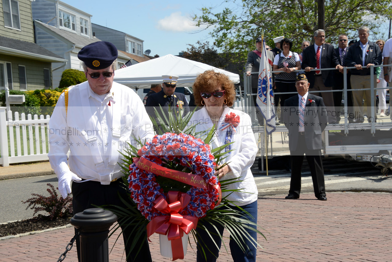 Sgt at Arms Jim Huges and President  Rosemary Carrollo from american legion 1029    carry a wreath monument in Island Park at the Memorial Day Services