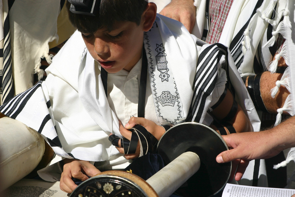 A  13 year old boy reads from the Torah, part of the tradition of becoming a Bar Mitzvah