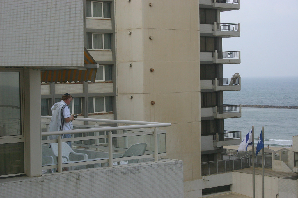 Looking out to the hotel next door, a man on the balcony greeted the early morning with prayer
