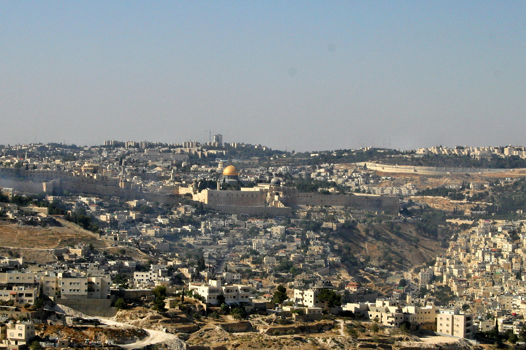 "A view of Jerusalem to the north, with the Dome of the Rock in the center. The old city walls are seen, and the surrounding ""new"" city dwarfs the old. Arab neighborhoods are in the foreground and the right; the other neighborhoods are mainly Jewish"