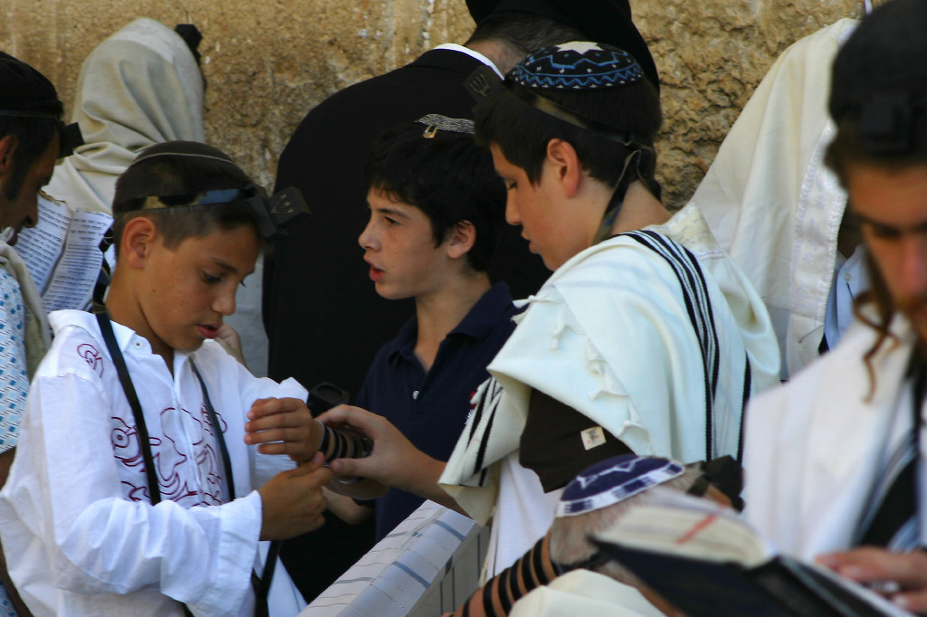 "Youngsters putting on T'fillin. These are boxes with prayers in them, wrapped with leather cords around the arm and the skull. This practice comes from Deuteronomy: in the same passage that commands us to revere the words of God by putting them ""on the doorposts of our house"" (also known as a Mezuza), the verse continues by commanding us to put them (God's words) before our eyes and upon our arms."