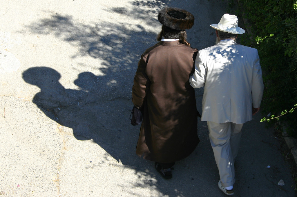 Sabbath (Shabbat) morning. Two friends chat on way to synagogue. Many sects of Judaism are represented in this city, the dress of the man on the left shows he belongs to a sect that hails from eastern Europe